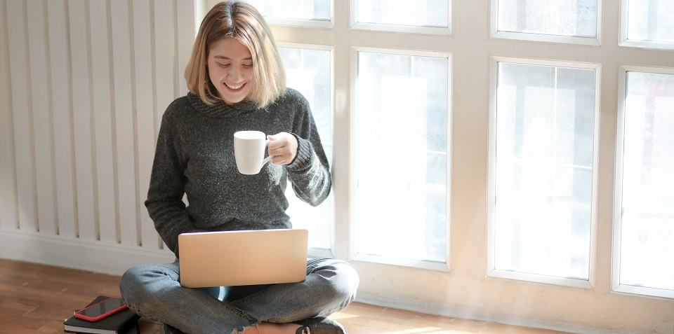 Woman sitting down drinking coffee whilst on laptop