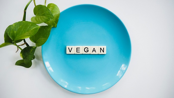 Blue plate with vegan written with scrabble letters